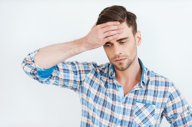 Hoffnungslosigkeit fühlen. frustrierter junger mann im hemd, der die stirn berührt