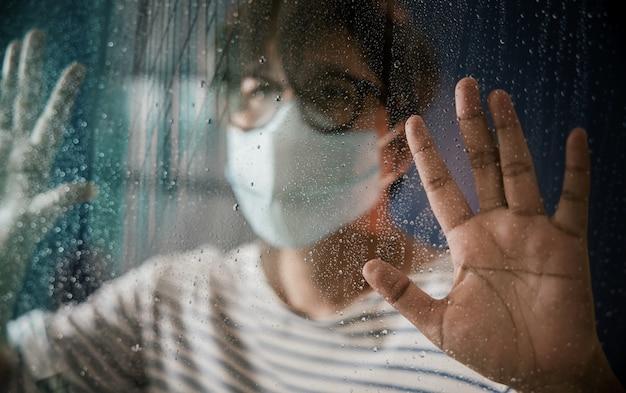 Hoffnungsvoll im coronavirus-situationskonzept. traurige person, die chirurgische maske im haus trägt und nach draußen durch das glasfenster in regnerischem tag schaut. selektiver fokus auf hand und regentropfen