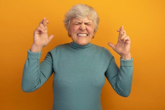 Hoffnungsvolle alte frau mit blauem rollkragenpullover, die viel glück mit geschlossenen augen macht, isoliert auf oranger wand?