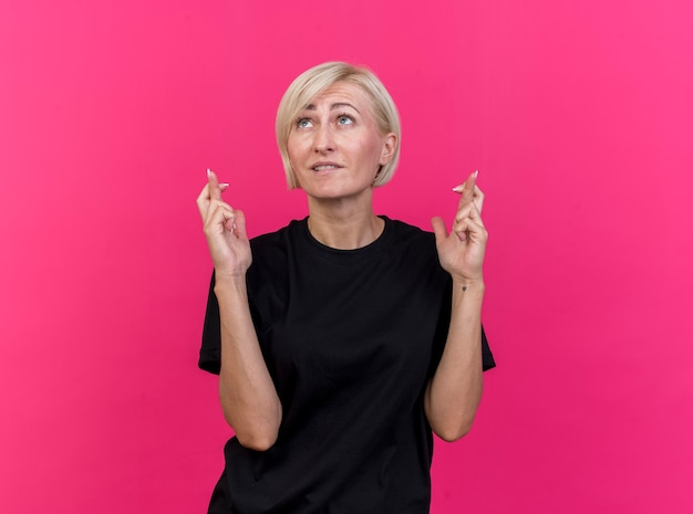 Hoffnungsvolle blonde frau mittleren alters, die glücksgeste tut, die lokal auf rosa wand nach oben schaut