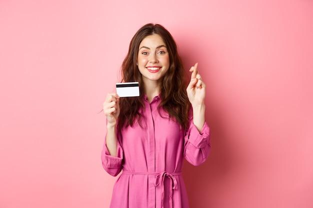 Hoffnungsvolle junge frau, die plastikkreditkarte und gekreuzte finger für viel glück zeigt, wunsch wünschend und lächelnd, gegen rosa wand stehend.