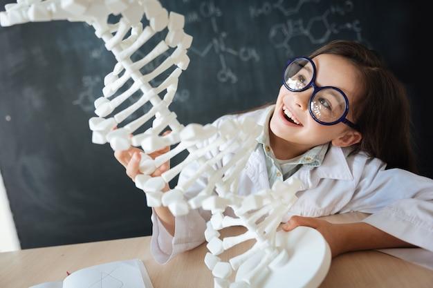 Hoffnungsvolle junge generation studiert. amüsiertes kluges schlaues kind, das im labor sitzt und biologieunterricht genießt, während es dna-modell lernt und erforscht