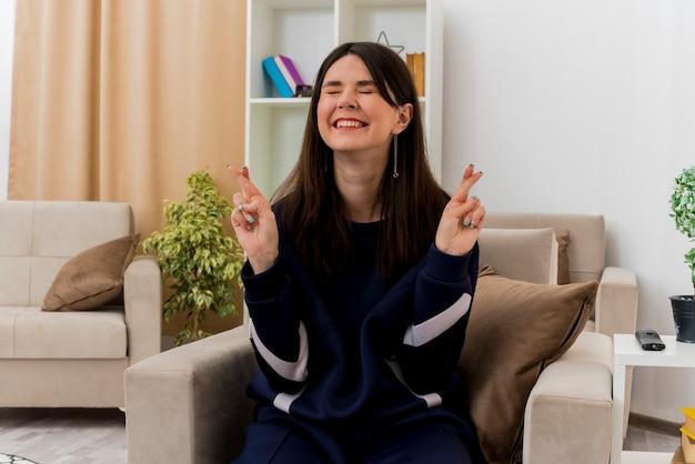 Hoffnungsvolle junge hübsche kaukasische frau, die auf sessel im entworfenen wohnzimmer sitzt, das finger kreuzt und mit geschlossenen augen viel glück wünscht