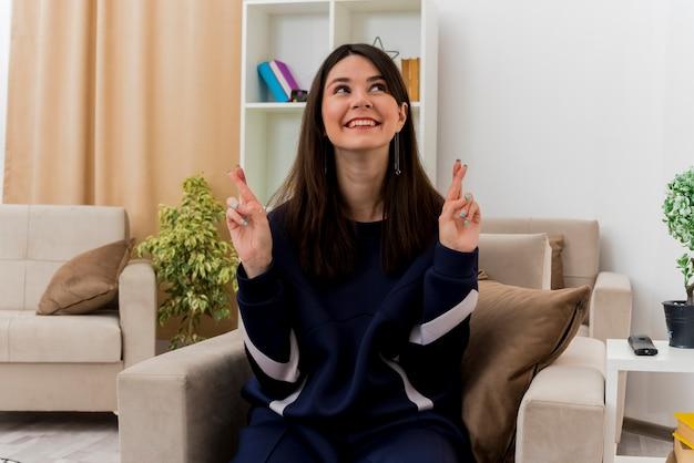 Hoffnungsvolle junge hübsche kaukasische frau, die auf sessel im entworfenen wohnzimmer sitzt, die seite betrachtet, die finger kreuzt und glück wünscht