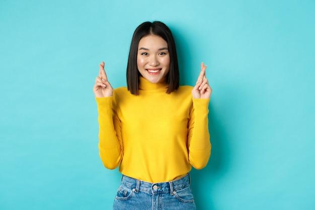 Hoffnungsvolle und optimistische asiatische frau kreuzen die daumen für viel glück, wünschen und lächeln, schauen in die kamera und erwarten etwas, stehen auf blauem hintergrund