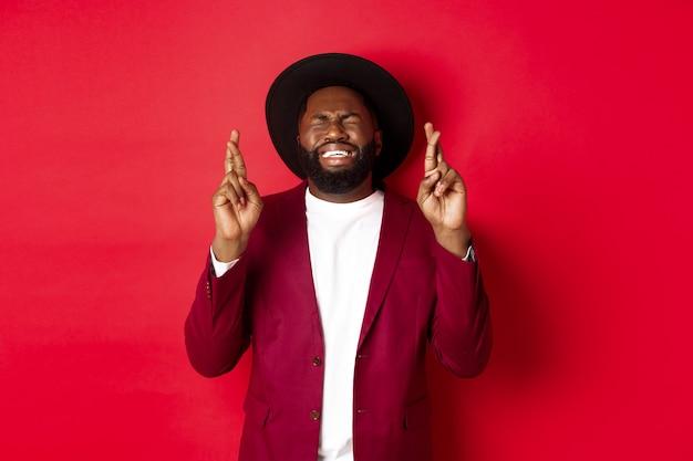 Hoffnungsvoller afroamerikanermann, der wunsch wünscht, daumen drückt für glück und optimistisch auf rot lächelnd lächelt