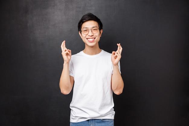 Hoffnungsvoller charismatischer asiatischer typ, der hofft, dass der deal gut läuft, daumen drücken, viel glück und optimistisch lächelnd, betend, wünschend, gute nachrichten erwartend, flehend