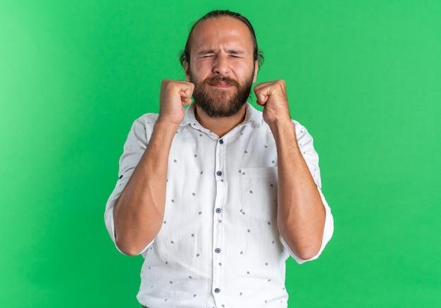 Hoffnungsvoller erwachsener, gutaussehender mann, der fäuste mit geschlossenen augen zusammenballt, isoliert auf grüner wand