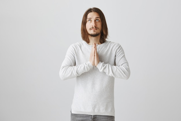 Hoffnungsvoller flehender junger mann, der aufschaut und hände im gebet hält