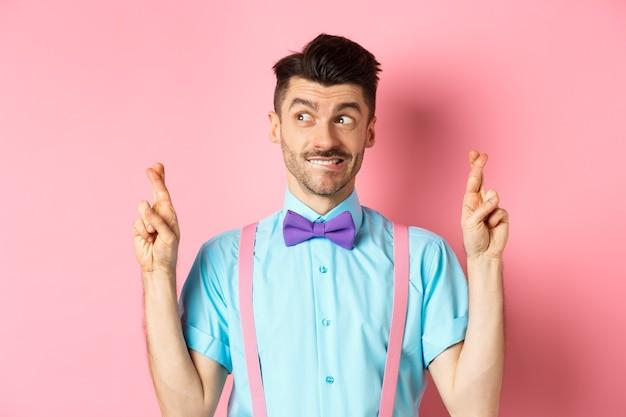 Hoffnungsvoller hübscher kerl in der fliege, der wunsch wünscht, daumen drücken für viel glück und nach links schauend, auf ergebnisse wartend oder betend, auf rosa hintergrund stehend.