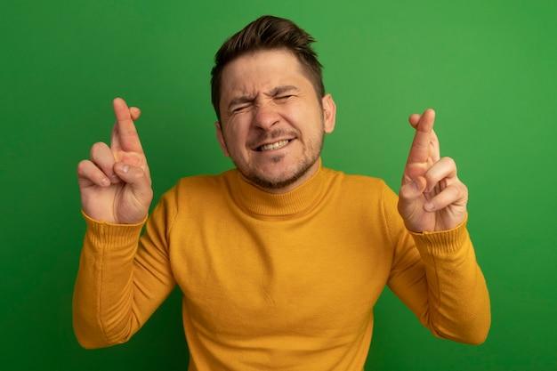 Hoffnungsvoller junger blonder gutaussehender mann, der die finger kreuzt und viel glück mit geschlossenen augen wünscht, die auf grüner wand isoliert sind?