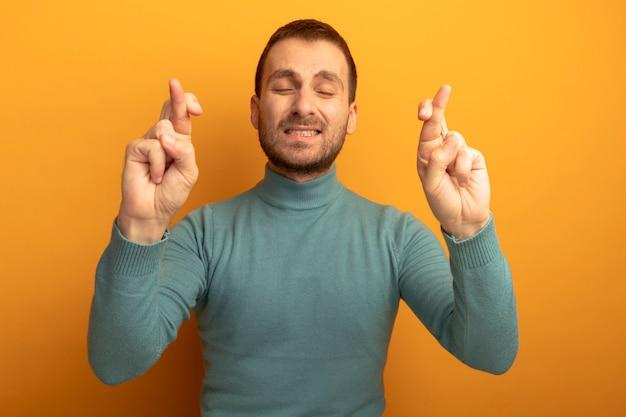 Hoffnungsvoller junger kaukasischer mann, der glücksgeste mit geschlossenen augen tut, die auf orange wand lokalisiert werden