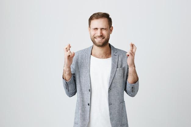 Hoffnungsvoller junger mann, der mit geschlossenen augen und gekreuzten fingern fleht