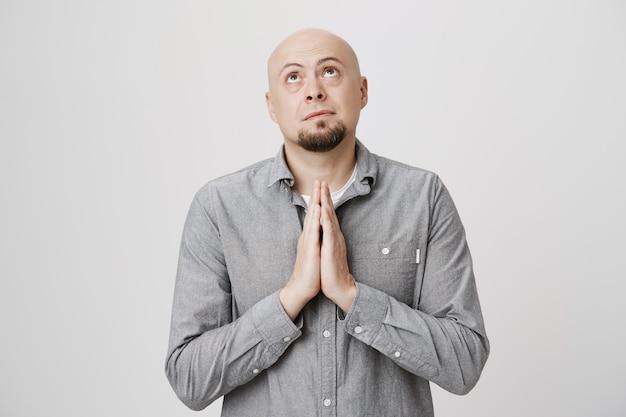 Hoffnungsvoller süßer glatzkopf, der fleht und zu gott betet