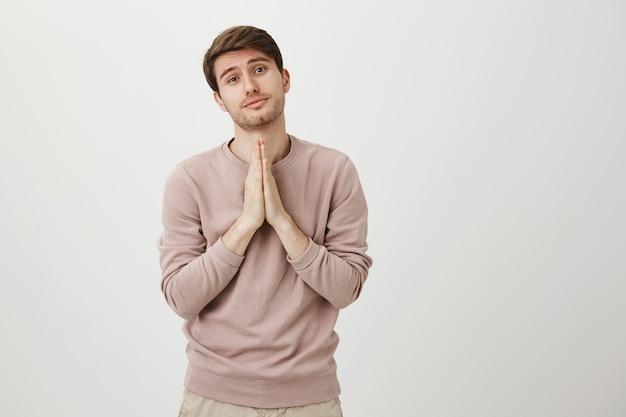 Hoffnungsvoller süßer mann, der um hilfe bittet, dich bittet oder bittet