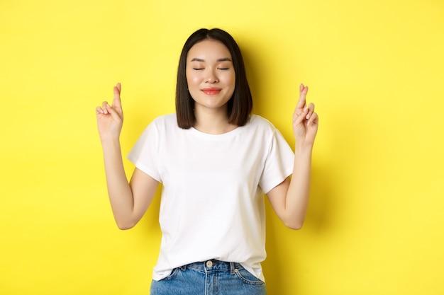 Hoffnungsvolles asiatisches mädchen, das wunsch wünscht, daumen drücken für viel glück und mit geschlossenen augen betend, bitte sagend, über gelbem hintergrund stehend.