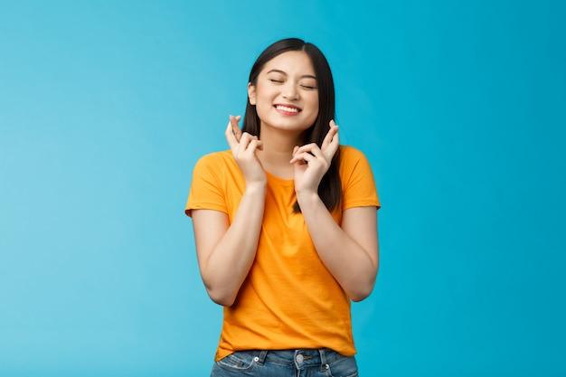 Hoffnungsvolles aufgeregtes asiatisches junges mädchen, das den wunsch macht, die finger zu kreuzen, viel glück, die augen schließen, die lächeln, glauben, den traum ...