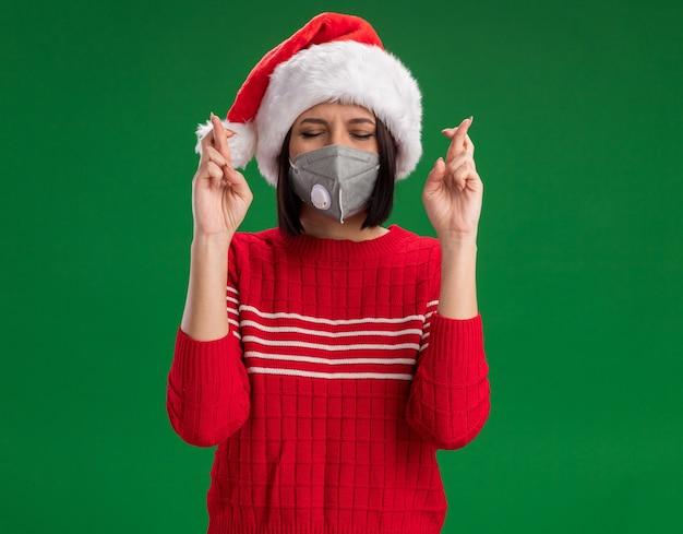 Hoffnungsvolles junges mädchen, das weihnachtsmütze und schutzmaske trägt, die glücksgeste mit geschlossenen augen tut, die auf grüner wand lokalisiert werden