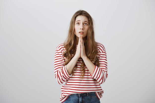 Hoffnungsvolles trauriges mädchen fleht, spricht mit gott oder betet