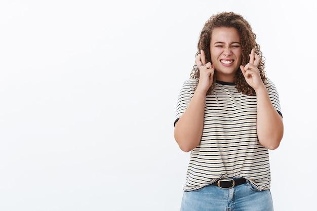 Hoffnungsvolles treues aufgeregtes süßes pralles mädchen mit lockigen zähnen begeistert gekreuzte finger viel glück beim warten auf gute positive ergebnisse