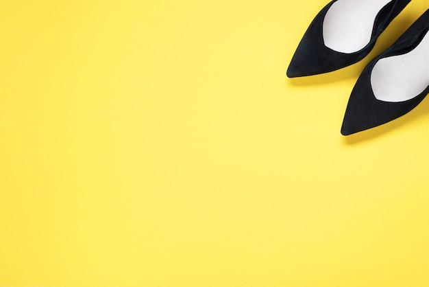 Hohe absätze der stilvollen schwarzen schuhe der mode auf gelbem hintergrund. flache lage, trendiger hintergrund der draufsicht. modeblog aussehen. fügen sie ihren text hinzu.