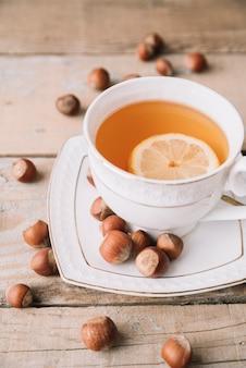 Hohe ansicht der tasse tee und der haselnüsse