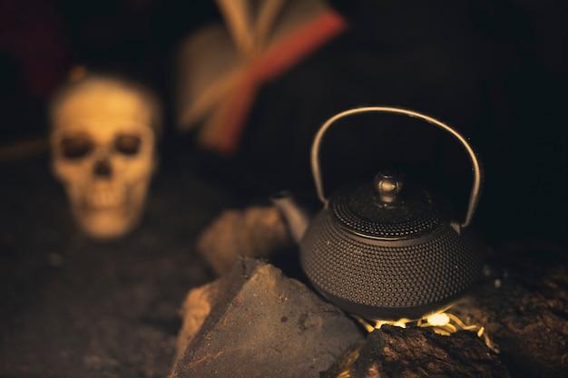 Hohe ansicht der teekanne mit dem unscharfen schädel im hintergrund