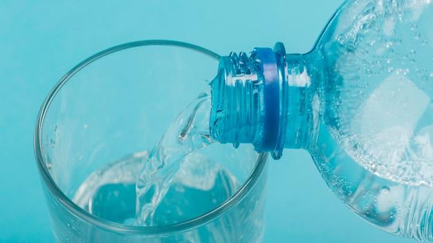 Hohe ansicht, die sprudelwasser in glas gießt