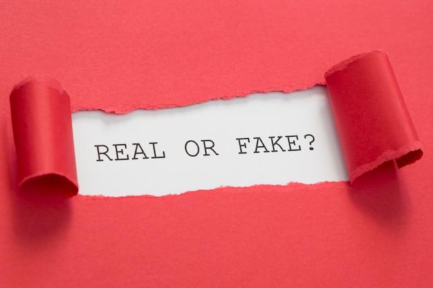Hohe ansicht echte oder gefälschte nachricht in zerrissenem rotem papier