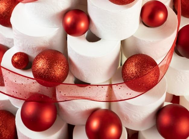 Hohe ansicht rote weihnachtskugeln und lametta auf toilettenpapierbaum