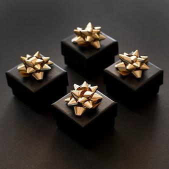Hohe ansicht schwarze geschenkboxen mit goldenen bändern