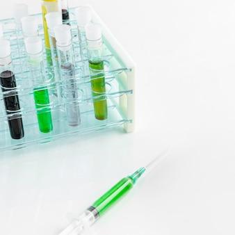 Hohe ansicht verschiedener chemieröhrchen und spritze