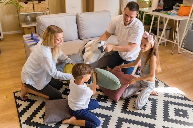 Hohe ansichtfamilie, die im wohnzimmer mit kissen spielt