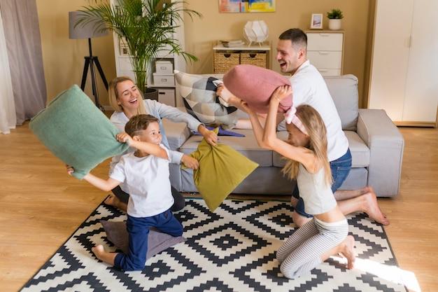 Hohe ansichtfamilie, die mit kissen spielt