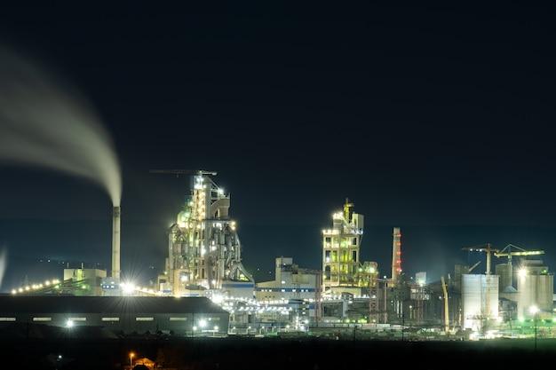 Hohe betonkonstruktion der zementfabrik mit turmdrehkran und rauchendem schornstein in der nacht. industrielle produktion und luftverschmutzungskonzept.