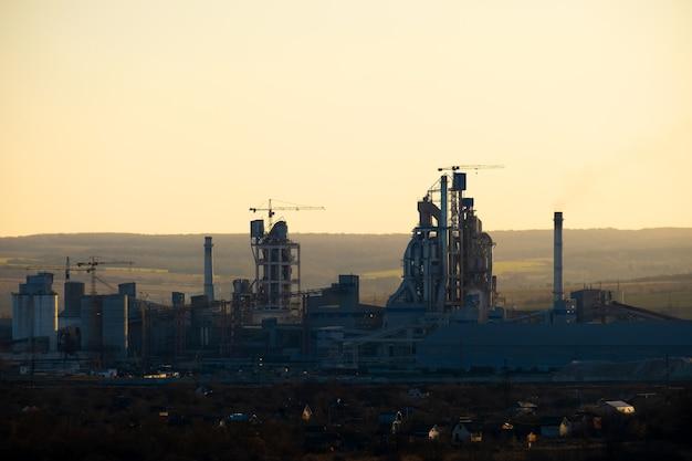 Hohe betonkonstruktion der zementfabrik mit turmdrehkran und rauchendem schornstein. industrielle produktion und luftverschmutzungskonzept.