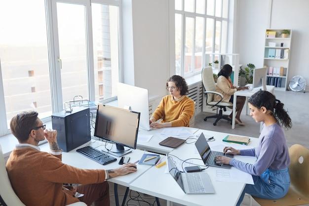 Hohe betrachtungswinkel bei diversen softwareentwicklungsteams mit computern am arbeitsplatz im weißen büroinnenraum, kopierraum
