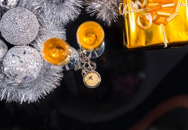 Hohe betrachtungswinkel der antiken taschenuhr auf dunkler glänzender tischoberfläche mit champagnergläsern, goldverpackten geschenken, silberner lametta-girlande und weihnachtskugeln - festliches stillleben mit textfreiraum