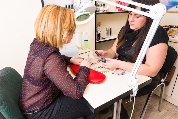 Hohe betrachtungswinkel der maniküre, die während der maniküre mit gemusterten nagelproben den weiblichen kunden blau gefärbten nagellack im spa zeigt