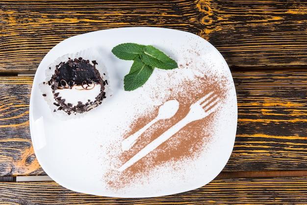 Hohe betrachtungswinkel des dekadenten desserts, das mit schokoladenspänen überzogen und auf einem teller mit minzblattgarnitur und utensilienkonturen serviert wird, die in kakao bestäubt sind und auf einer holztischoberfläche ruhen