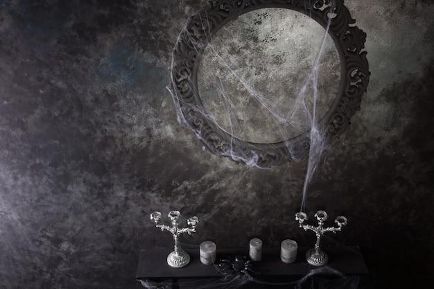 Hohe betrachtungswinkel des dekorativen runden rahmens über kerzen und kandelabern auf unheimlichem, mit spinnweben bedecktem mantel in spukhaus-einstellung
