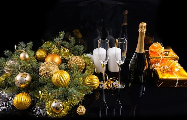 Hohe betrachtungswinkel des festlichen stilllebens - flasche champagner mit eleganten gläsern auf schwarzem hintergrund mit geschenken, kerzen und dekorierten evergreens mit weihnachtskugeln und lametta