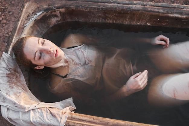 Hohe betrachtungswinkel einer depressiven frau mit geschlossenen augen, die im freien mit schmutzigem wasser in der badewanne liegt