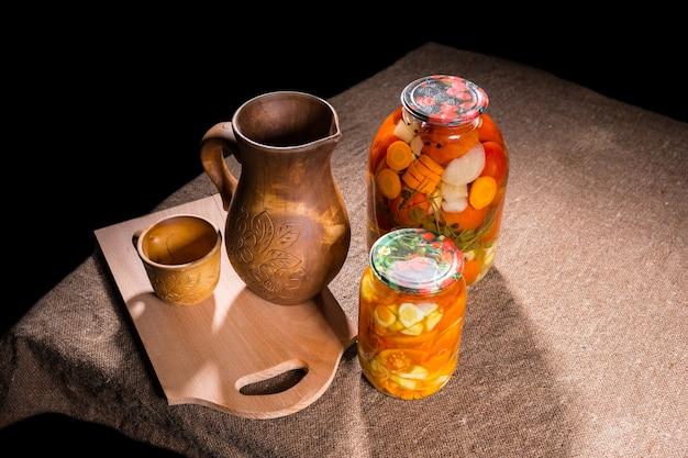 Hohe betrachtungswinkel von gläsern mit eingelegten gemüsekonserven auf der tischoberfläche neben geschnitztem holzhandwerk - holzkrug, tasse, schüssel und holzschneidebrett mit textfreiraum