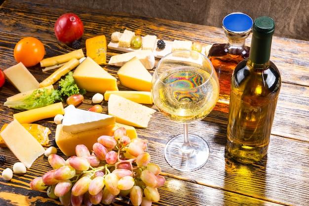 Hohe betrachtungswinkel von glas weißwein auf rustikalem holztisch mit flaschen, verschiedenen käsesorten und frischem obst