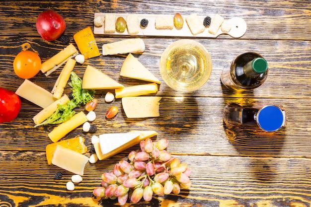 Hohe betrachtungswinkel von gourmet-käse, obst und weißwein auf rustikalem holztisch mit textfreiraum