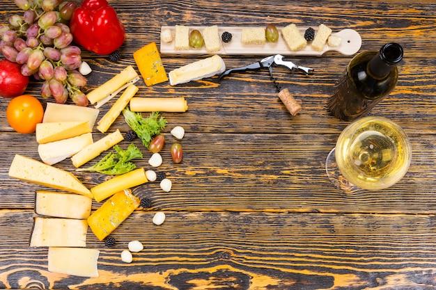 Hohe betrachtungswinkel von gourmet-käse und frischem obst mit glas weißwein und flasche auf rustikalem holztisch mit zentralem textfreiraum