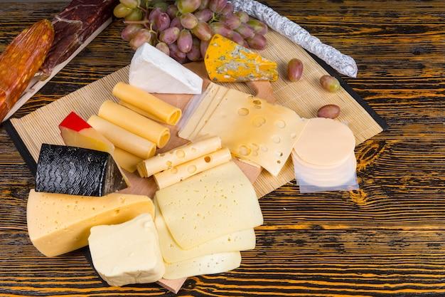 Hohe betrachtungswinkel von gourmet-käsebrett mit großer käseauswahl und garniert mit obst, serviert auf rustikalem holztisch mit textfreiraum