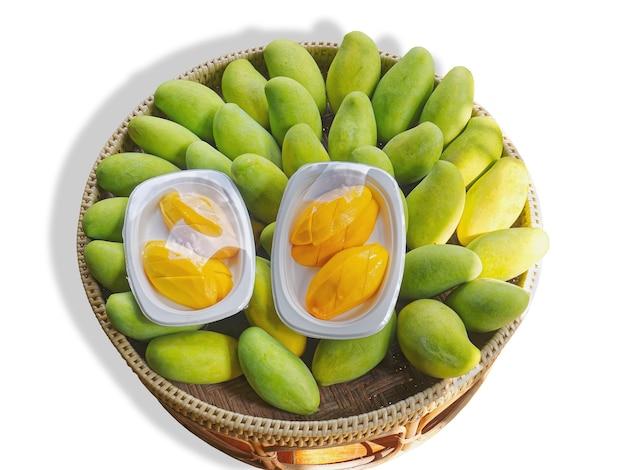 Hohe betrachtungswinkel von haufen von frischen grünen mangos und packungen mit geschnittenen mangos im korb, isoliert auf weiss