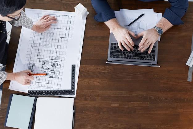 Hohe betrachtungswinkel von ingenieuren, die am laptop arbeiten und am holztisch den bauplan für neue konstruktionen zeichnen